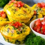 Egg muffins on a serving plate topped with diced tomatoes.