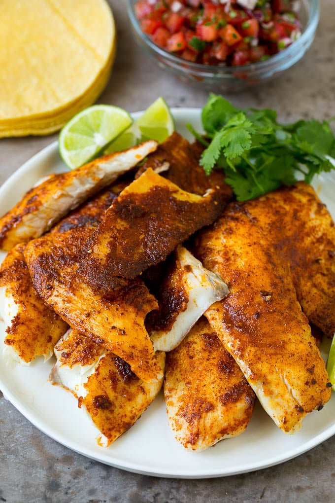 A plate of taco seasoned fish fillets with a lime and cilantro garnish.