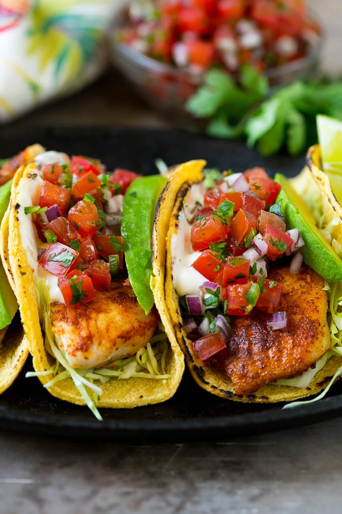 Fish tacos with cabbage, avocado, salsa and creamy sauce.