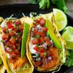 Fish tacos wrapped in corn tortillas with sliced avocado and pico de gallo.
