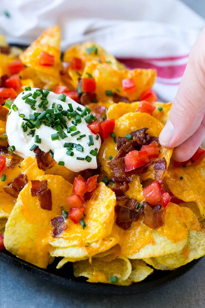 Irish nachos loaded with cheese, bacon, sour cream, tomatoes and chives.