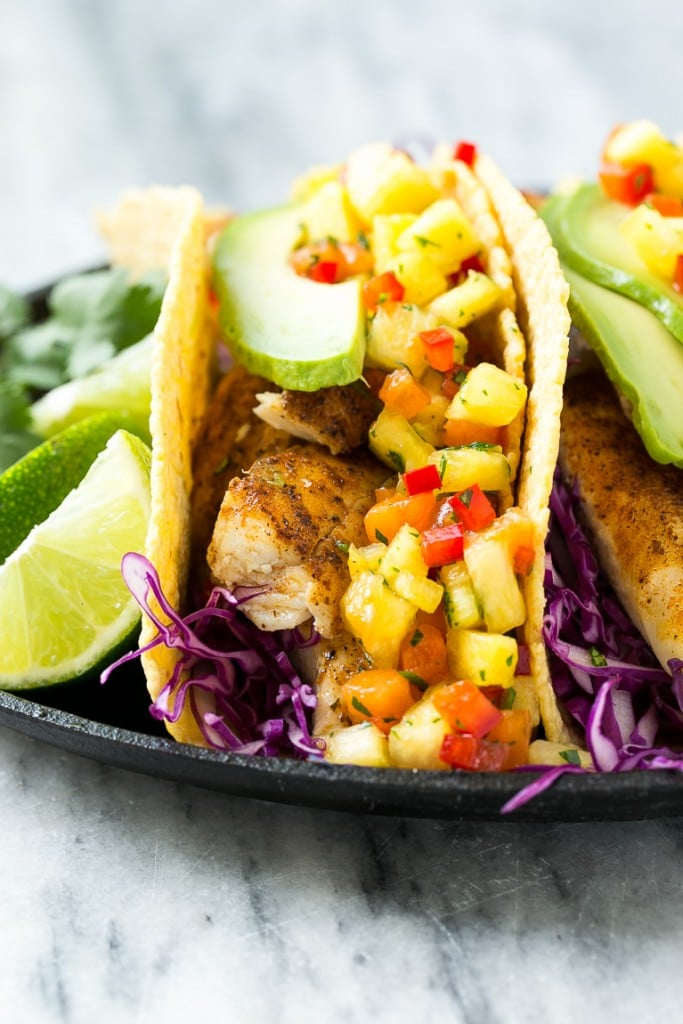 This recipe for tilapia fish tacos is seasoned fish layered with cabbage, avocado and a tropical salsa, all tucked inside warm corn tortillas. It's a meal that's fast, fresh, healthy and ready in 20 minutes!