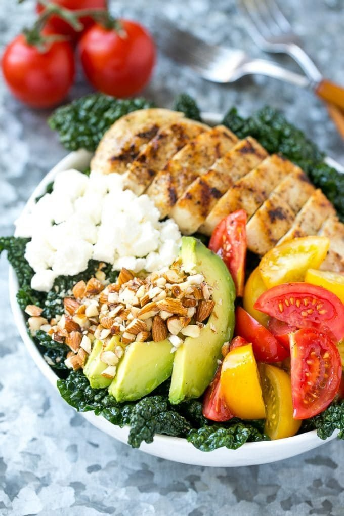 A bowl of Tuscan kale salad with grilled chicken, tomatoes, avocado and feta cheese.