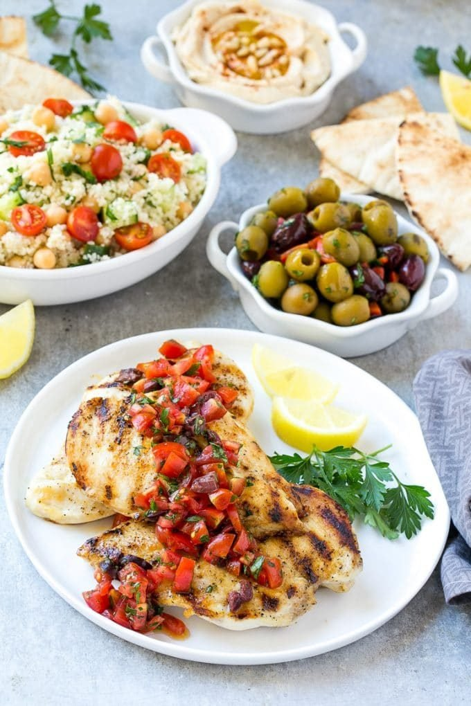 Grilled chicken, olives, couscous, hummus and pita bread.
