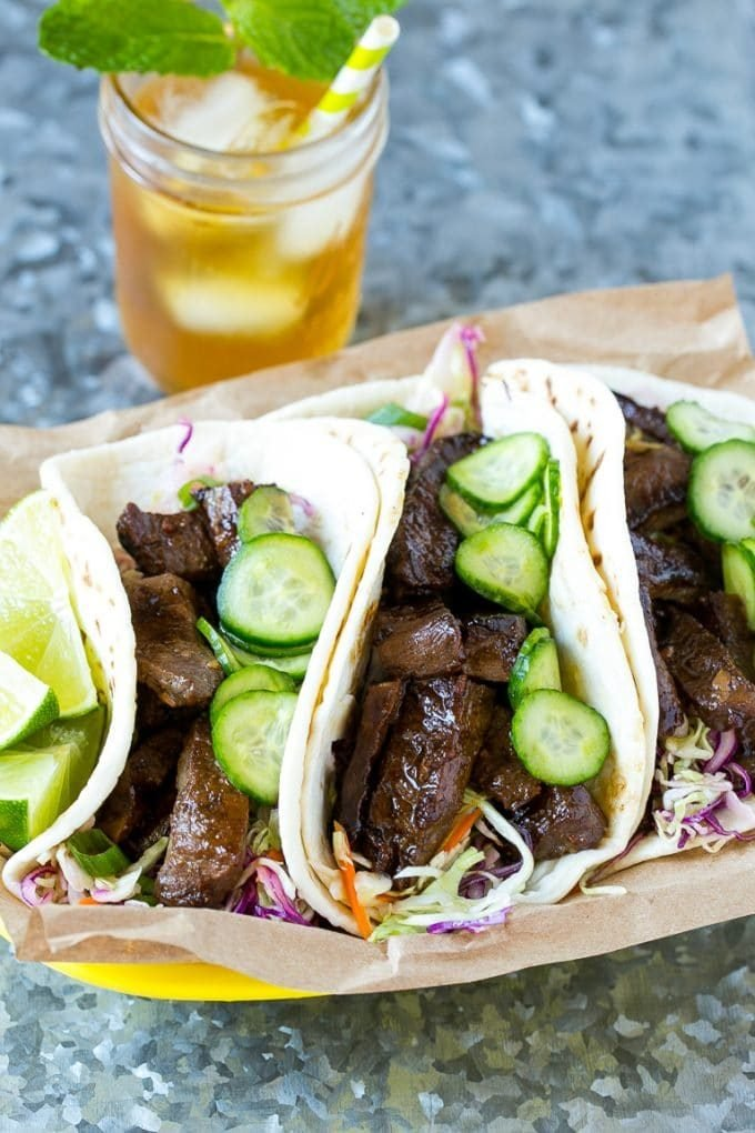 A basket of Korean beef tacos served with iced tea.