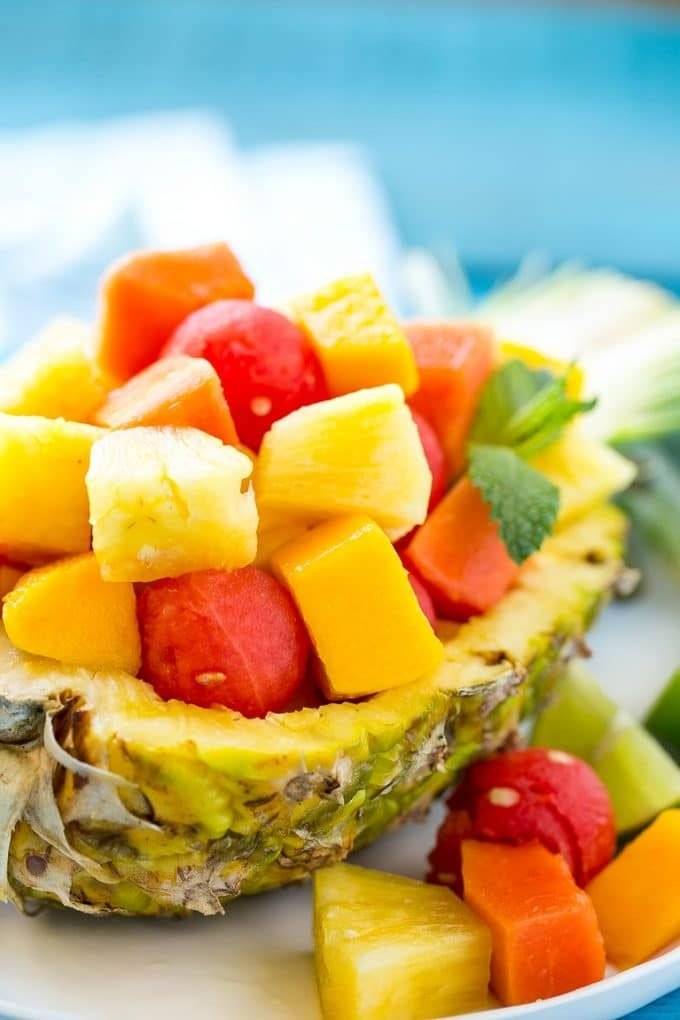A pineapple half filled with melon, papaya and mango.