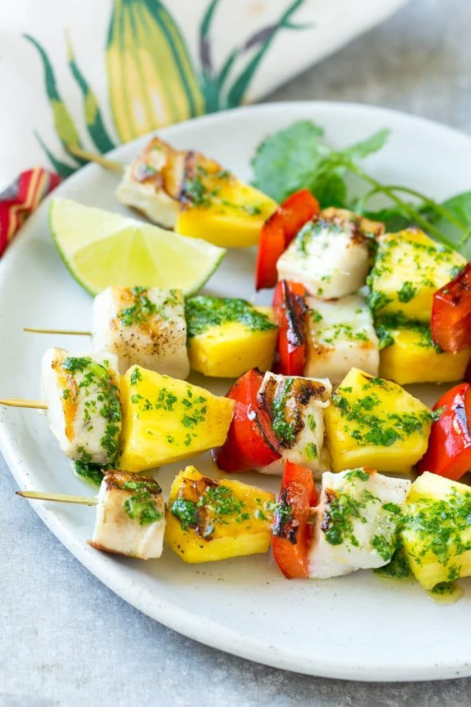 Mojo fish kabobs with lime wedges and cilantro for garnish.