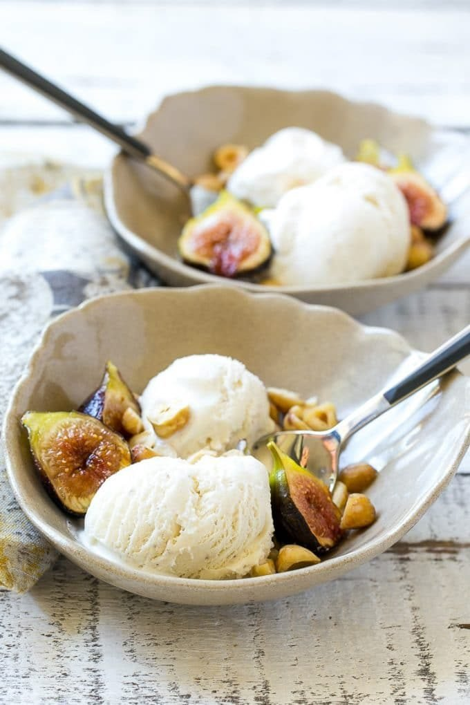 Bowls of ice cream with halved figs, toasted hazelnuts and serving spoons.