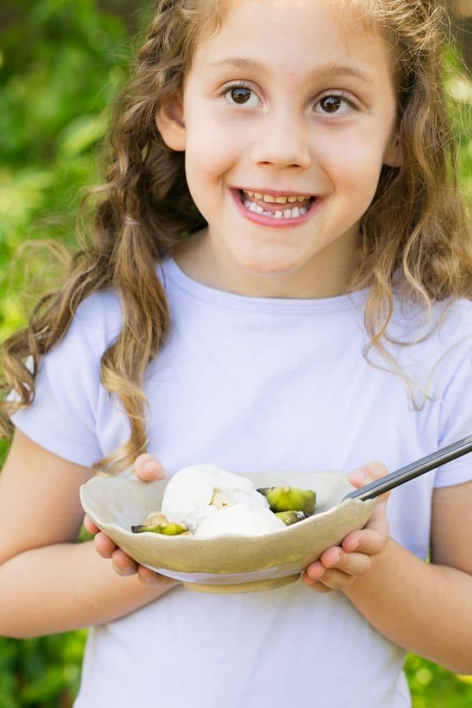 A girl holding a bowl of roasted figs with ice cream.