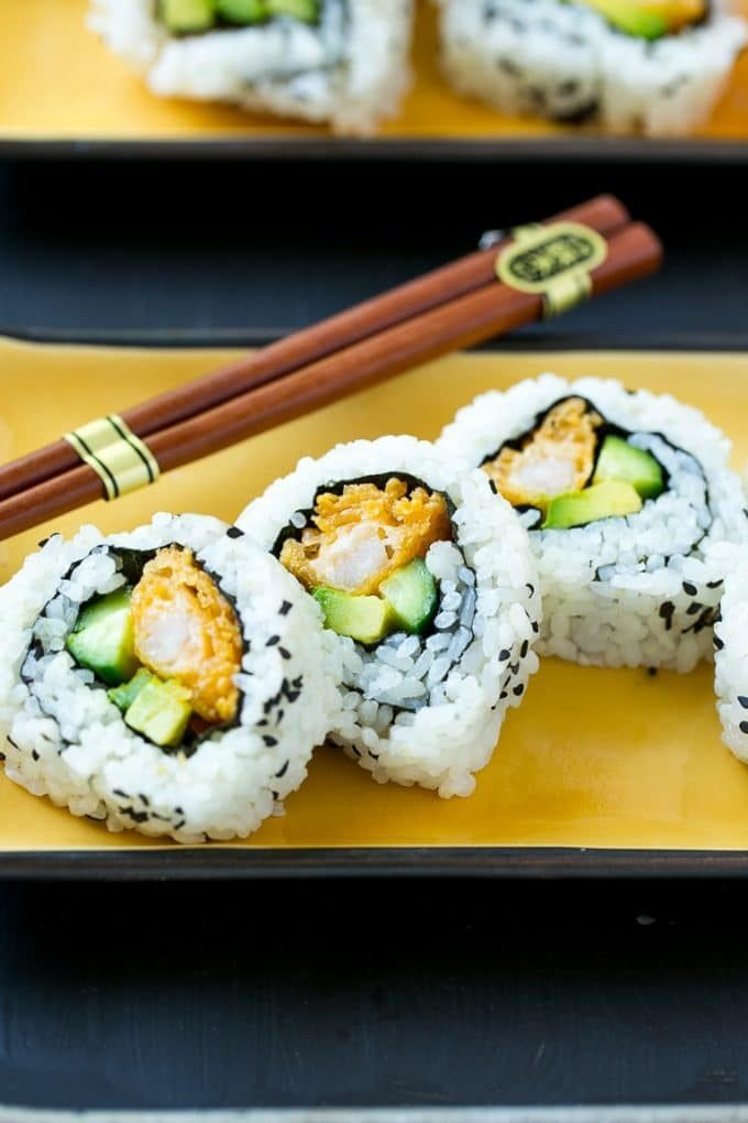 Sliced shrimp tempura roll sushi on a serving plate.