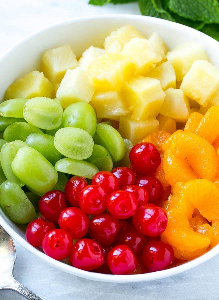 A bowl of oranges, pineapple, grapes and cherries.