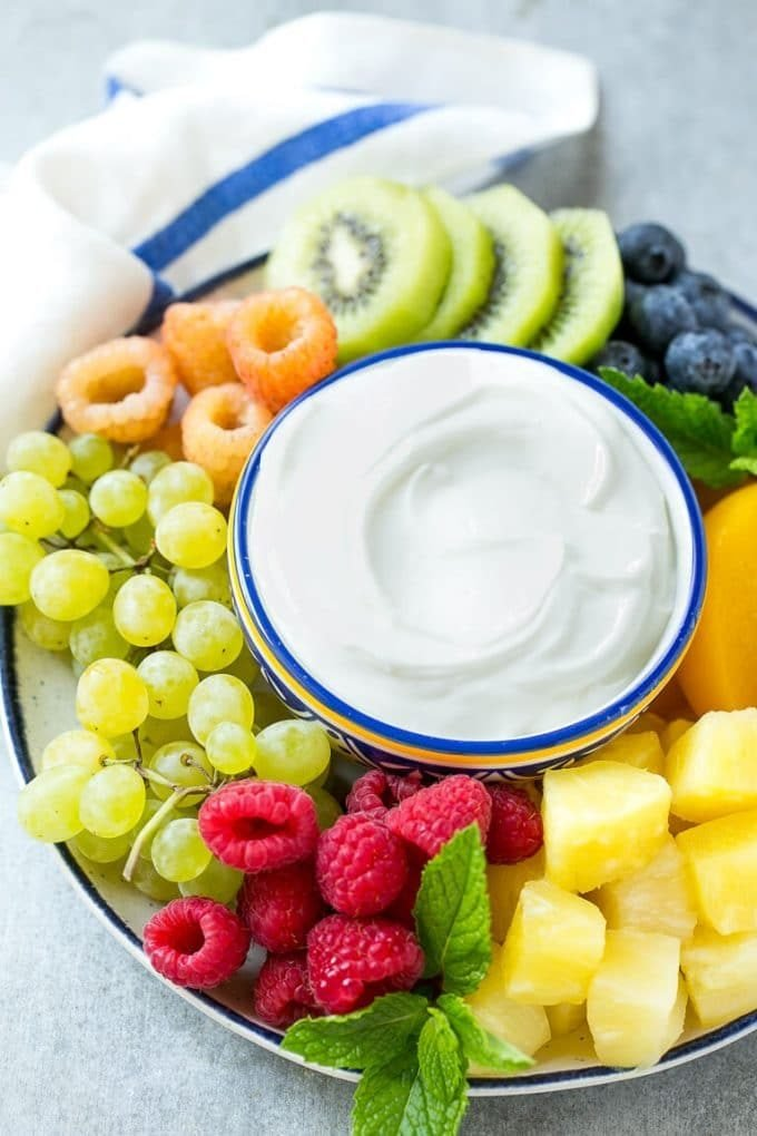 A bowl of cream cheese fruit dip surrounded by colorful fruit.