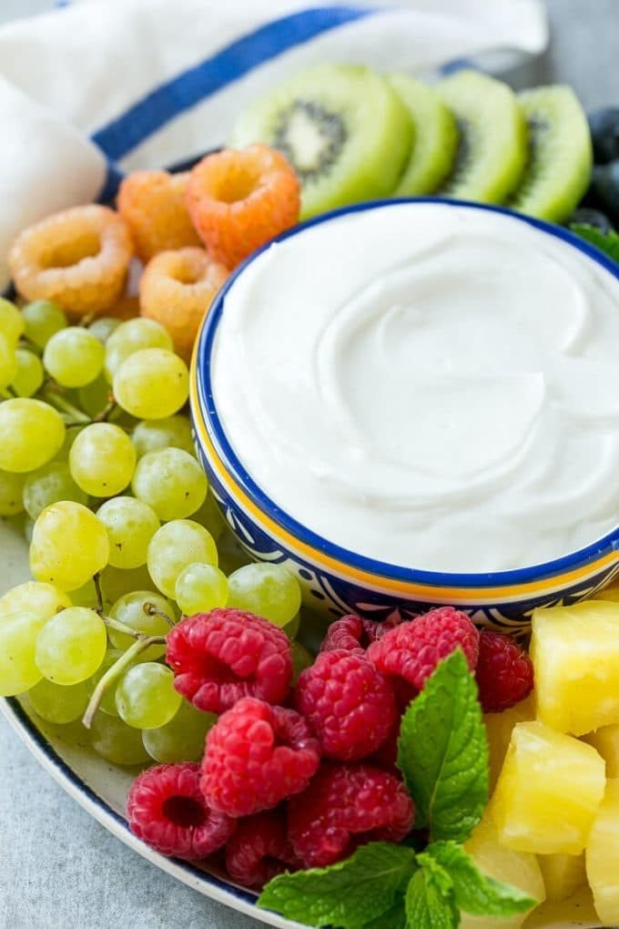 A bowl of cream cheese fruit dip surrounded by grapes, raspberries and kiwis.