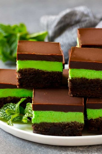 Layered mint brownies with frosting on a serving plate, garnished with fresh mint.