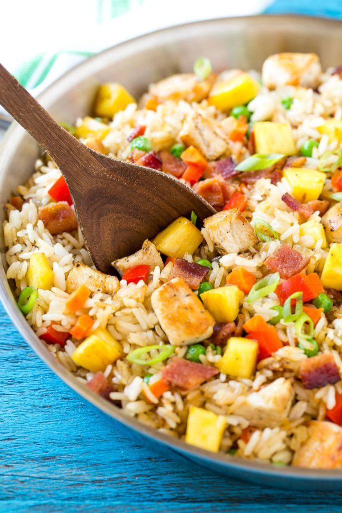 This recipe for pineapple fried rice is loaded with chicken, bacon, crunchy veggies and juicy pineapple. A simple and easy main course or side dish that's MUCH better than take out!