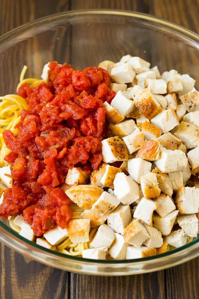 Diced chicken, tomatoes and spaghetti in a bowl.