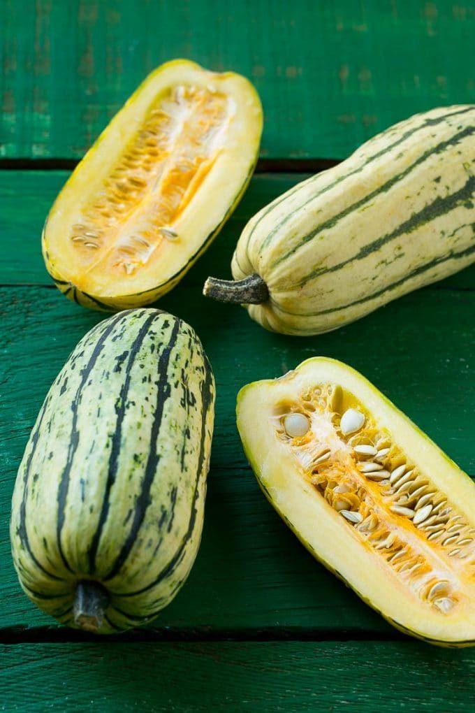 Raw delicata squash on a green board.