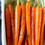 Honey roasted carrots in a baking dish, garnished with chopped parsley.