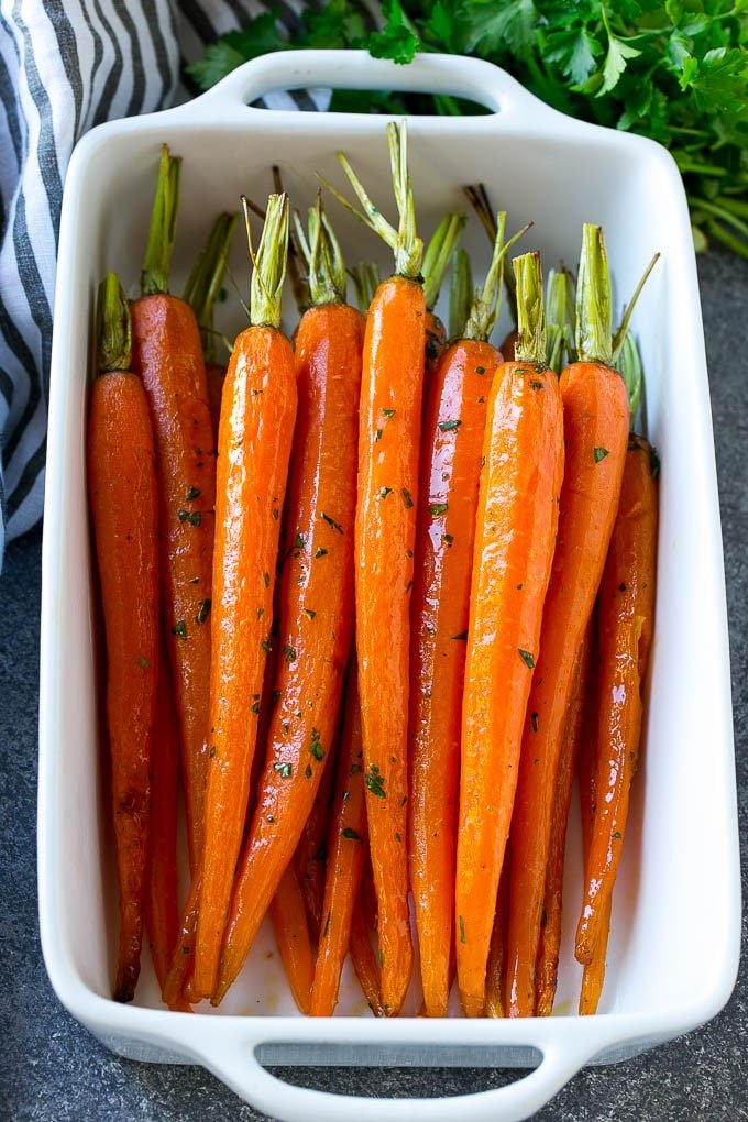 A baking dish of honey roasted carrots topped with parsley.