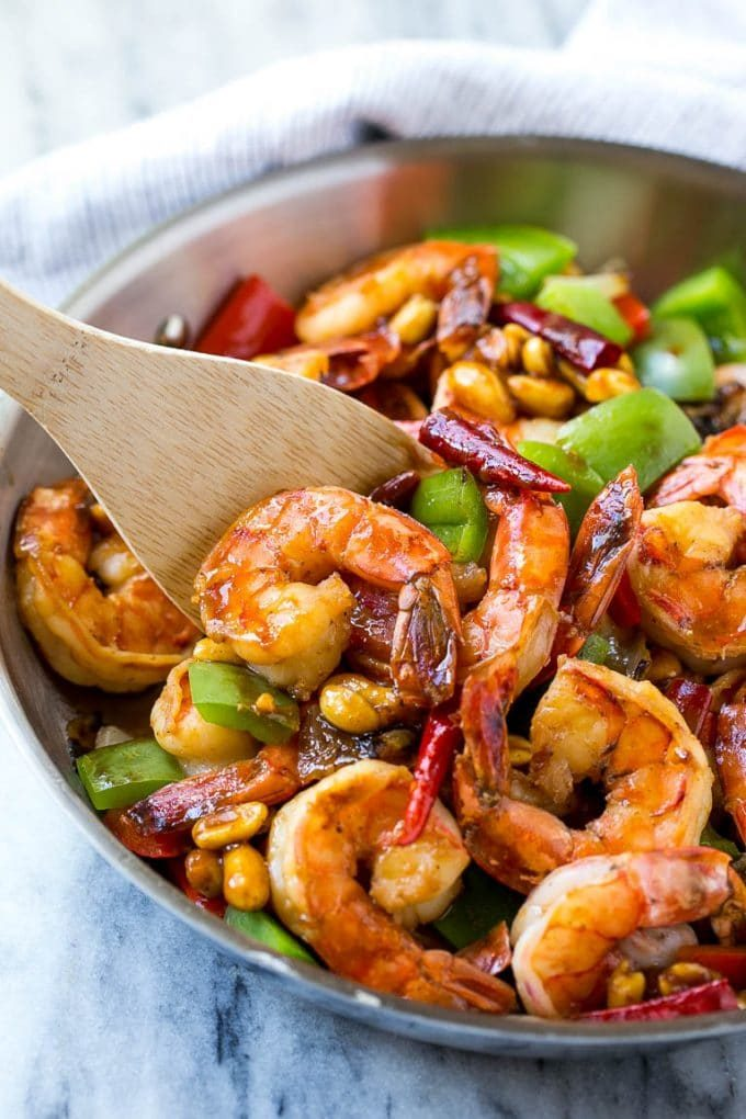 A serving spatula in a pan of Kung Pao shrimp.