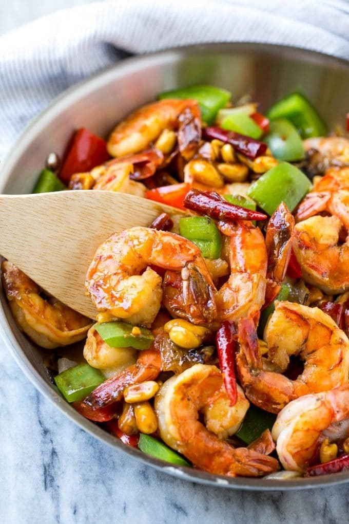 A skillet of spicy shrimp with peanuts and vegetables.