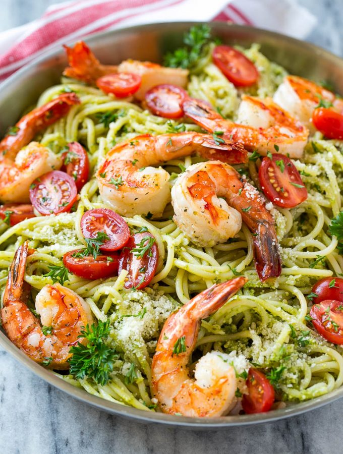 This recipe for shrimp pesto pasta is spaghetti tossed in a flavorful pesto sauce, then topped with sauteed shrimp and tomatoes. A fresh and easy dinner that's quick to make and packed with flavor!