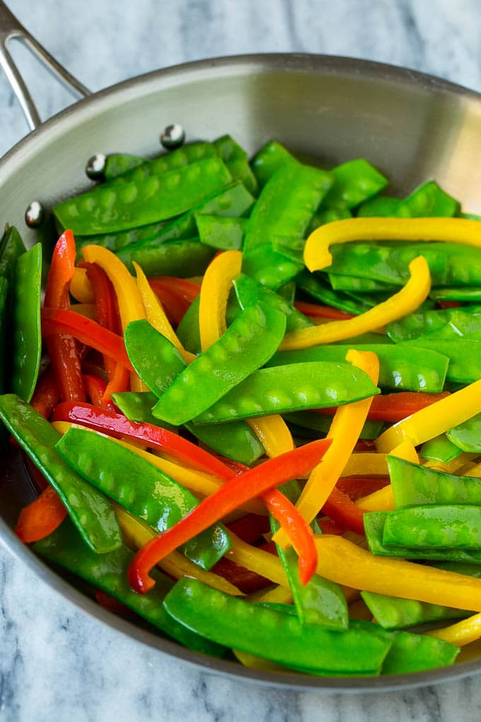 Cooked snow peas and bell peppers in a skillet.
