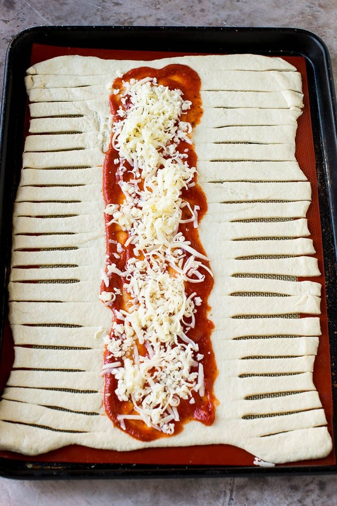 A sheet of pizza dough topped with tomato sauce and mozzarella cheese.