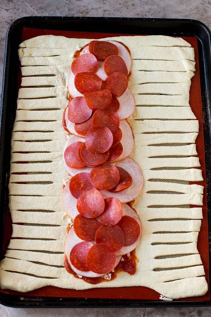 A sheet of pizza dough topped with tomato sauce, mozzarella cheese, pepperoni and Canadian bacon.