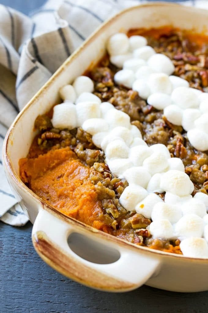 Sweet potato casserole with marshmallows and pecan streusel, with a spoonful removed.