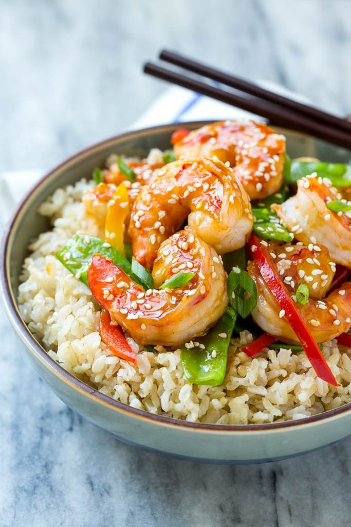 A bowl of shrimp stir fry and vegetables garnished with sesame seeds.