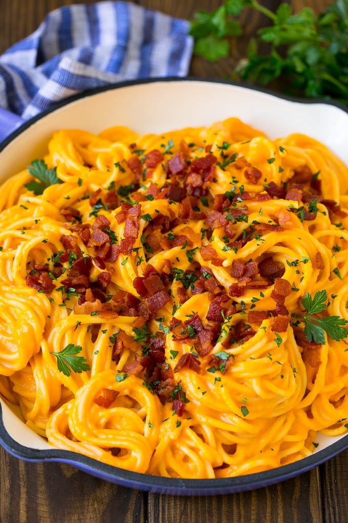 Butternut squash pasta in a skillet topped with bacon and parsley.