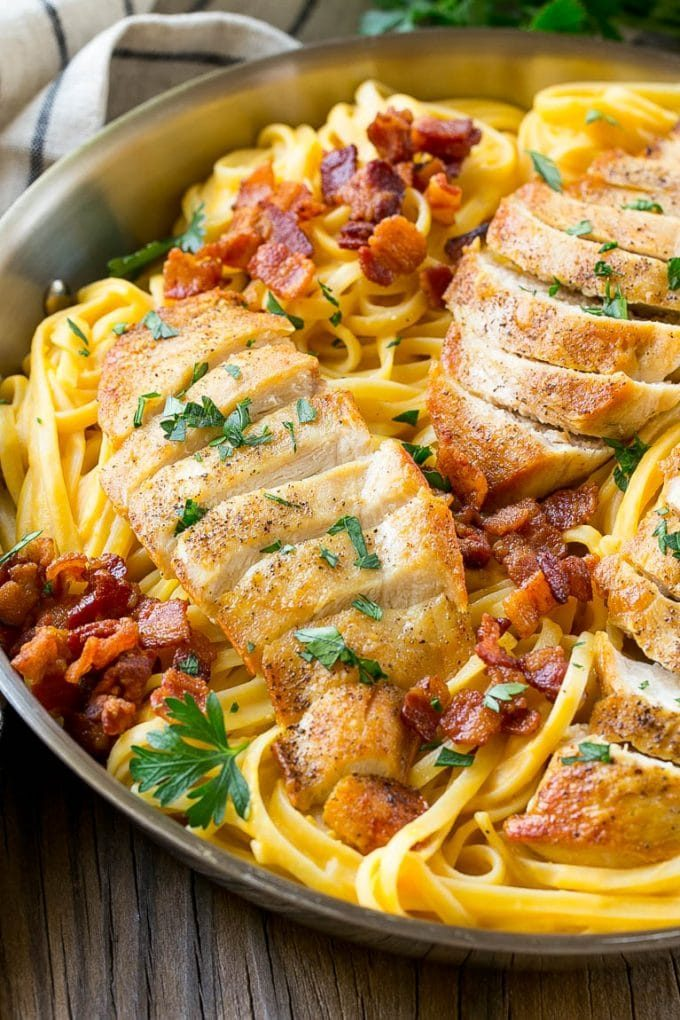 Sliced seared chicken served over butternut squash pasta with bacon.