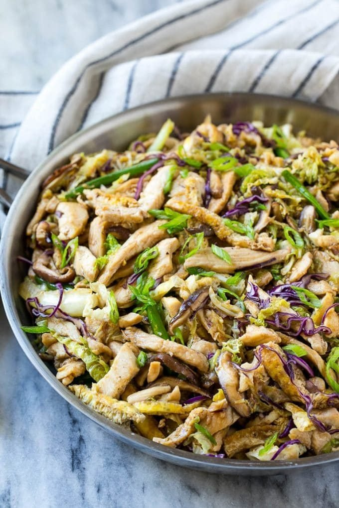A skillet of moo shu chicken with eggs, cabbage and mushrooms.