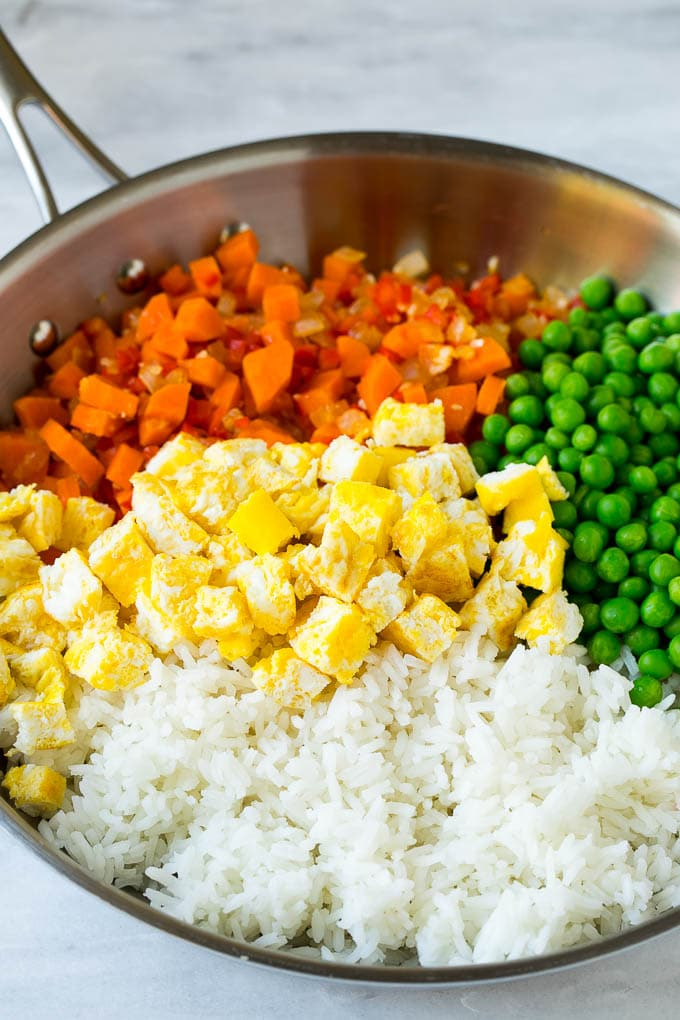 Vegetables, scrambled egg, rice and peas in a frying pan.
