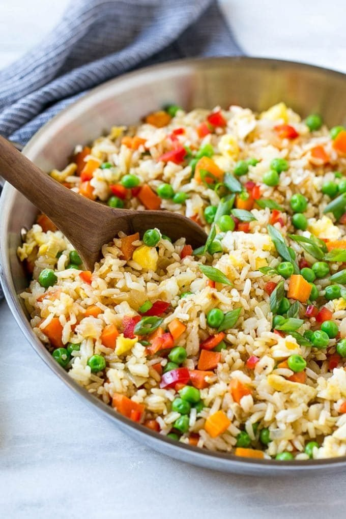 Veggie fried rice in a skillet with a serving spoon.