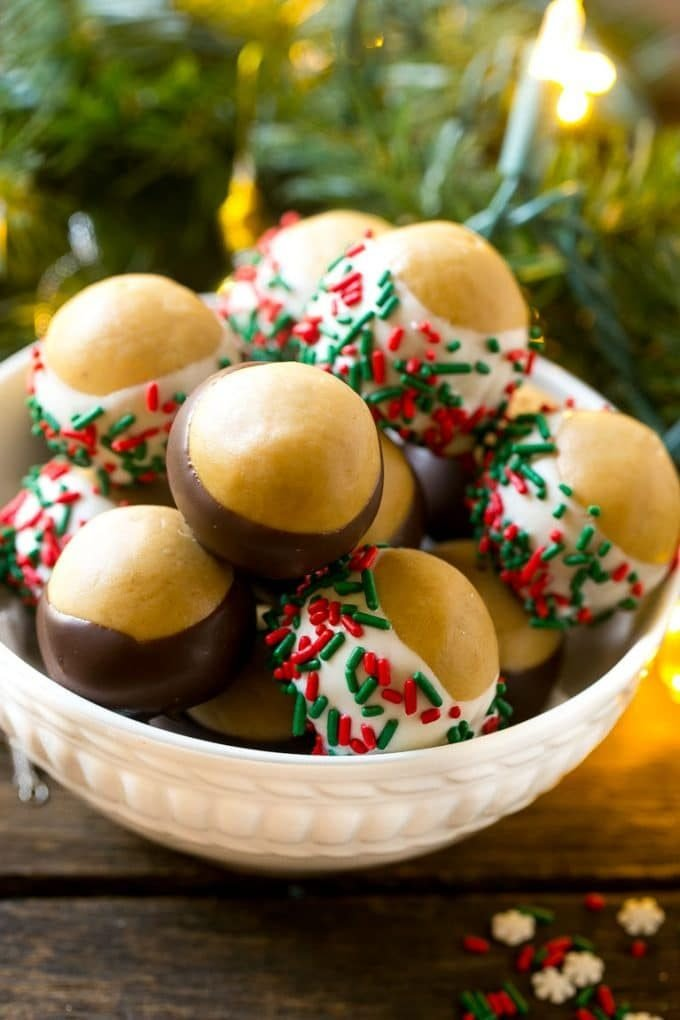 Chocolate Covered Peanut Butter Balls on a plate, decorated with holiday sprinkles.