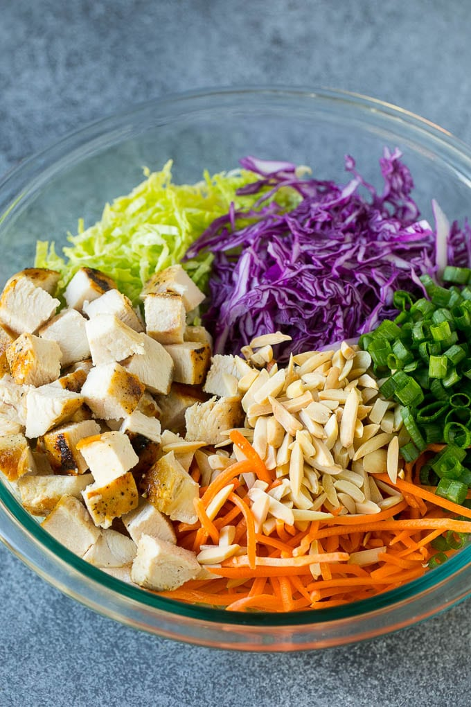 Cabbage, carrots, chicken, almonds and green onions in a bowl.