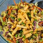 A bowl of Chinese chicken salad topped with wontons and sesame seeds.