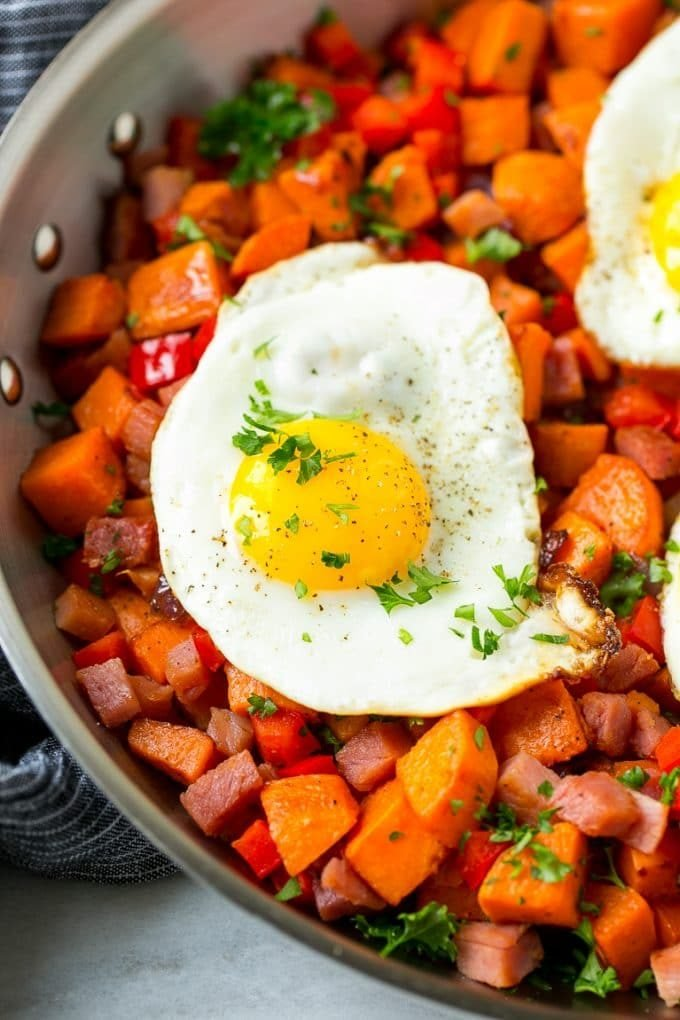 A fried egg served over sweet potatoes, ham and vegetables.
