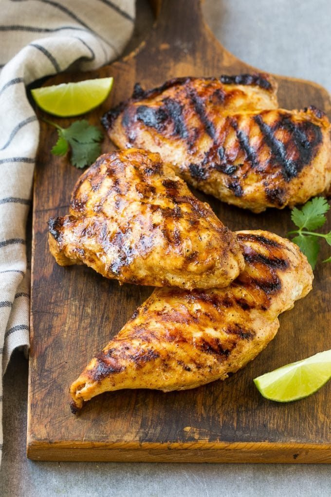 Grilled chicken breasts on a cutting board.