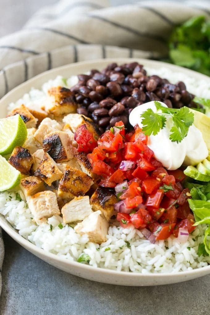 A burrito bowl with an assortment of toppings including chicken, beans, lettuce and fresh salsa.