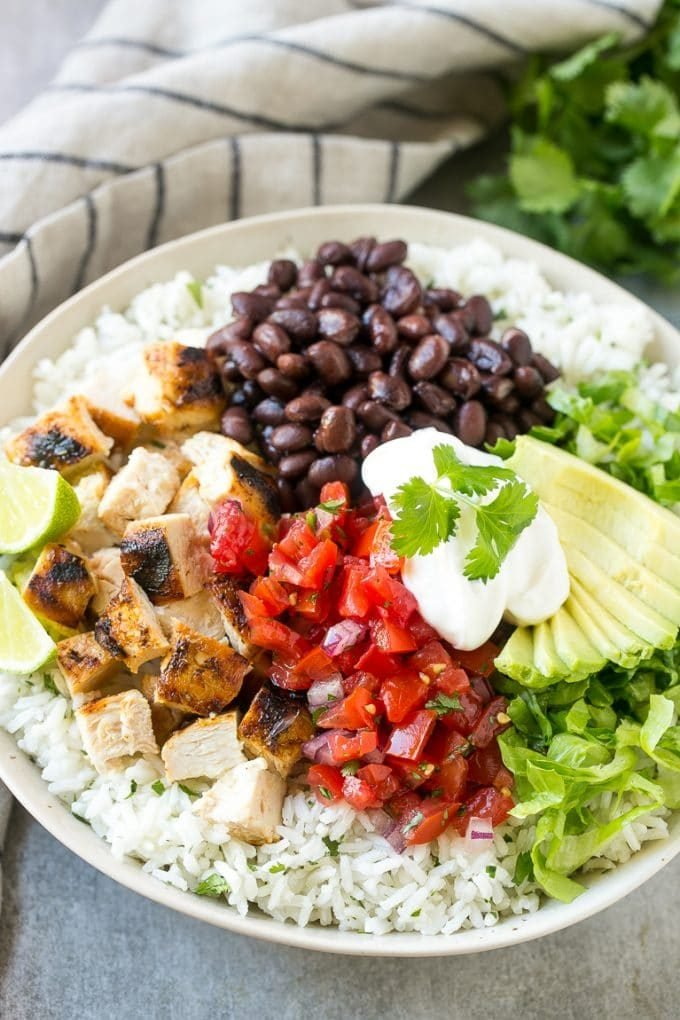 Burrito bowls with rice, chicken, salsa, beans and avocado.
