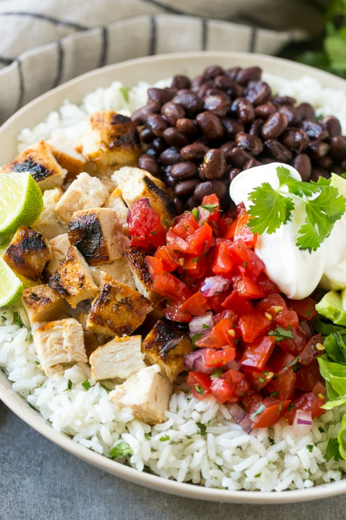 A bowl filled with cilantro lime rice, chicken, beans, sour cream and salsa.