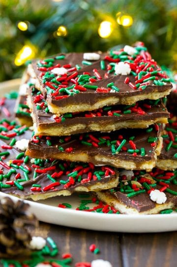 Christmas crack toffee topped with holiday sprinkles on a serving plate.