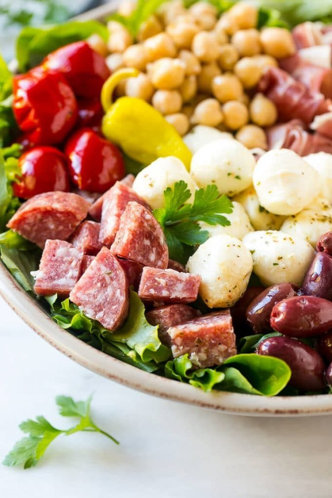 A bed of greens topped with antipasto salad including meats, cheeses, beans and vegetables.