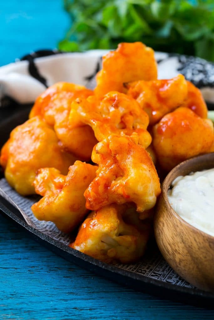 This recipe for buffalo cauliflower bites is crispy cauliflower florets baked to perfection and coated in spicy buffalo sauce. Serve with ranch dip for the ultimate game day snack!