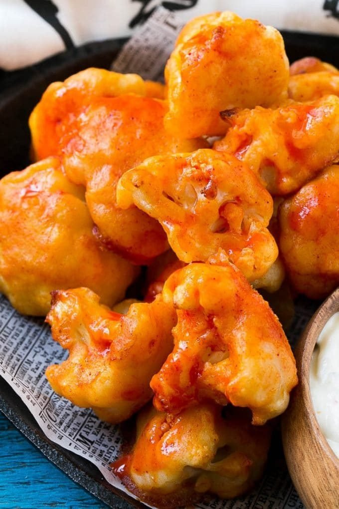 Buffalo cauliflower bites coated in hot sauce.