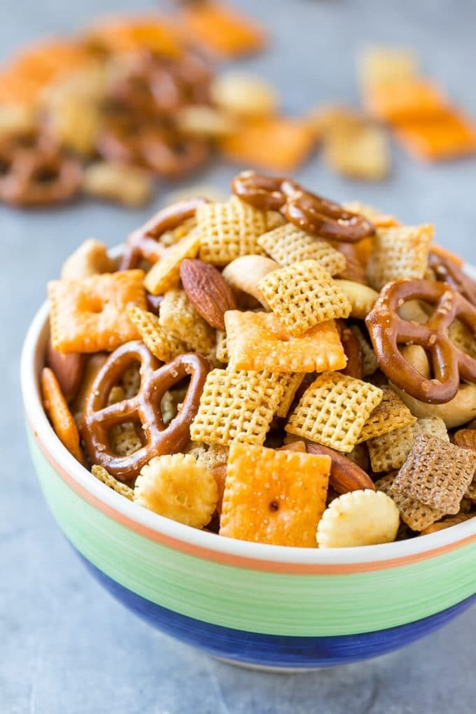 A bowl of chex mix which contains cereal, almonds, cashews, oyster crackers, cheese crackers and prtezels.