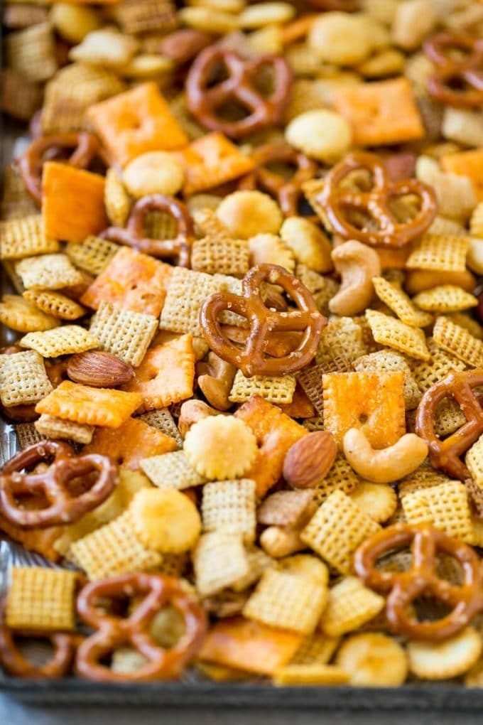 A tray of from scratch chex mix that's made with chex cereal, mixed nuts, pretzels and two kinds of crackers.